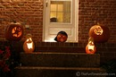 Lighted pumpkins on a porch step.