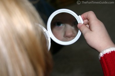 A little girl lookin at herself in the mirror.